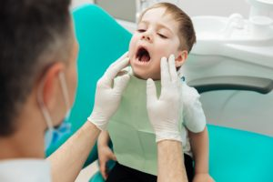 Dentist checking for tooth decay to apply fissure sealants in Chelsea MA